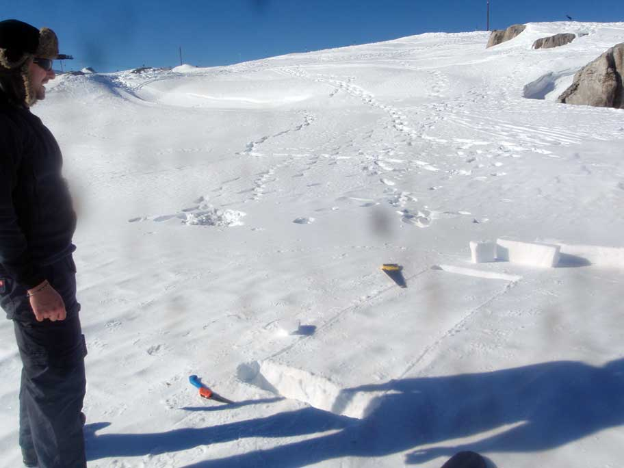 Rob cutting blocks from the snow on a mountaintop