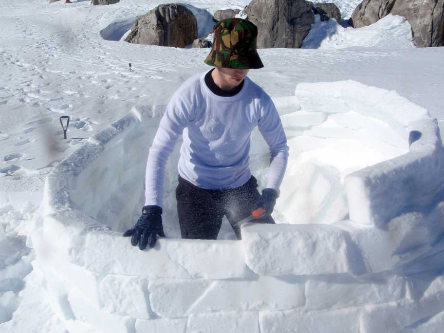 Leo shaping blocks on a half-finished igloo
