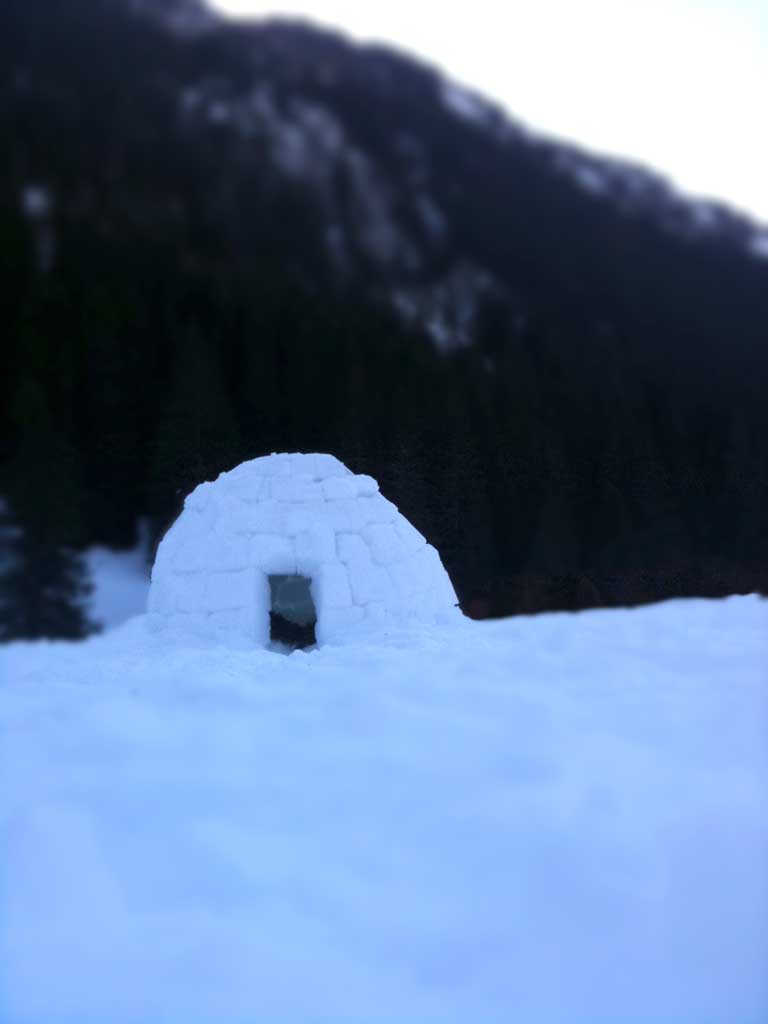 An igloo shadowed by mountains beyond