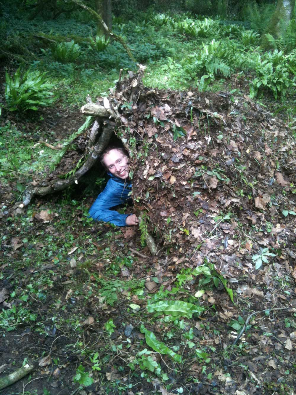 Leo Critchley in a debris shelter in the woods