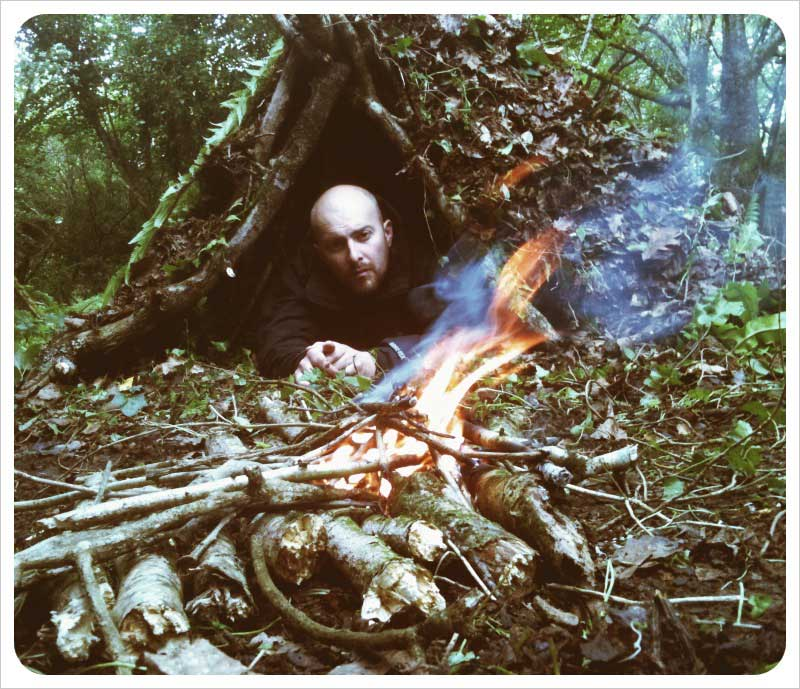 Rob Cowen in a debris shelter in the woods with a fire