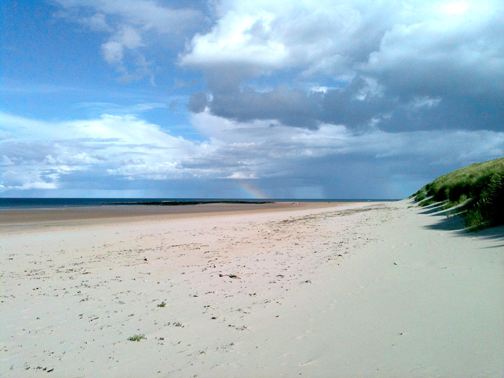 A white sandy beach, blue sky and a rainbow
